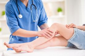 Gydytoja apžiūri pacientės koją