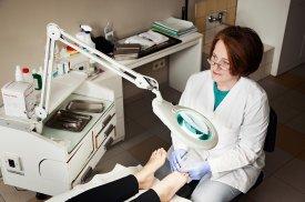 Gydytoja konsultuoja pacientę pėdų priežiūros klausimais
