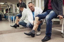 Ortopedas technologas pacientui parodo individualiai pagamintą protezą