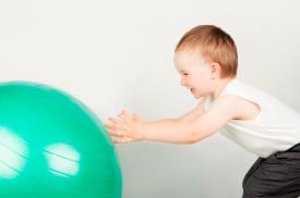 Vaikas atlieka pratimus su kamuoliu